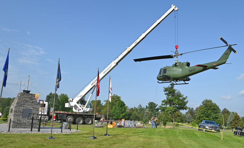 LIFTED Up — A crane lifts a freshly repainted helicopter and carefully begins the process of moving it to its pedestal at the Vietnam Veterans Memorial on the Griffiss Business and Technology Park on Thursday. The effort is part of Phase 2 of the memorial. Anyone wishing to make a tax-deductible donation to the memorial project, may send them to the New York State Vietnam Veterans Memorial Fund, Inc., 210 Elm St., Rome, N.Y. 13440.