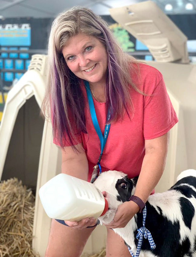 FEEDING TIME — Volunteer Terri DiNitto helps a newborn calf with its milk bottle at the New York State Fair Dairy Cow Birthing Center. There is still time to experience the birthing center — the last day of the fair is Labor Day.