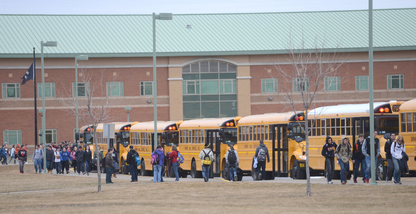 GET COMFORTABLE — Rome Free Academy students walk to their buses after dismissal from school in this file photo. Members of the district's Board of Education were critical of early pickups and long bus rides during a special meeting on Thursday.