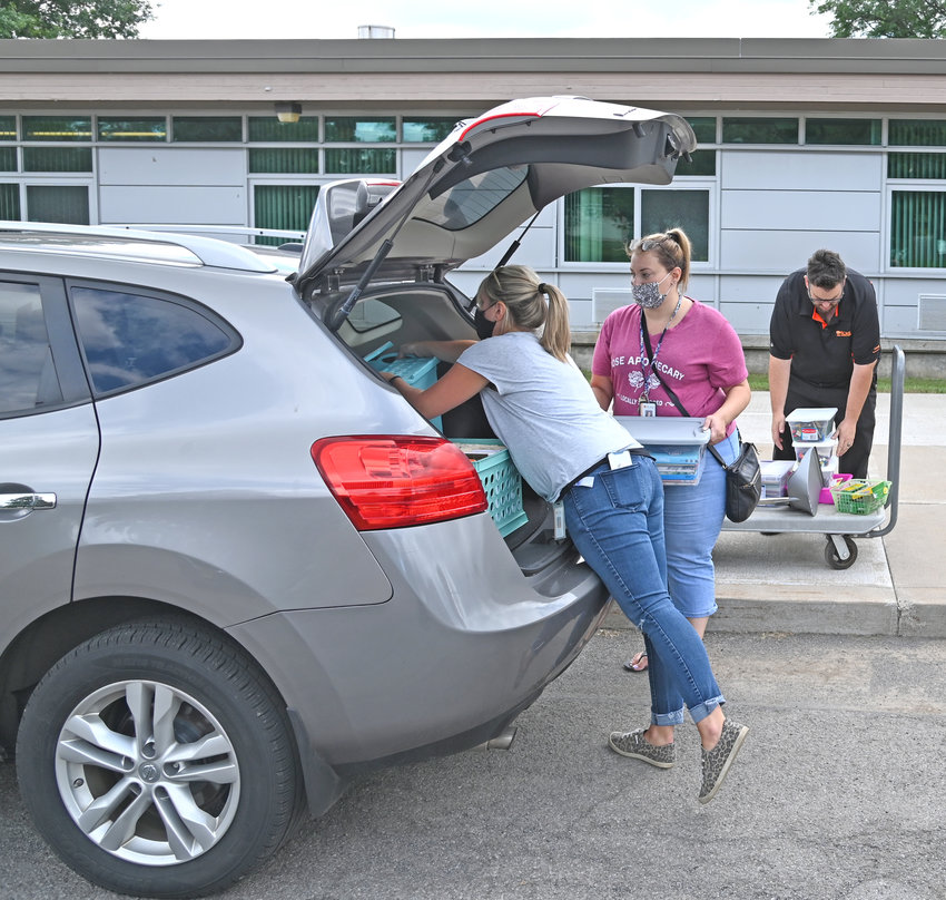 """MOVING TO A NEW SCHOOL —Third grade teacher Bobbi Cook, left, and Samantha Kahler load up their cars with items from their classrooms at Staley Elementary School, 620 E. Bloomfield St., to a new room at Gansevoort Elementary School, 758 W. Liberty St. In addition to the relocation across the city, the two will go from having separate classrooms at Staley to """"team teaching"""" in one room in their new building."""
