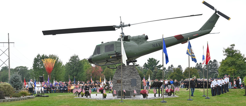 HELICOPTER DEDICATED —A large crowd turns out for the dedication of a helicopter monument at the Vietnam Veterans Memorial on the Griffiss Business and Technology Park on Sunday. The aircraft has been painstakingly rehabbed and painted to honor those who served during the Vietnam War.