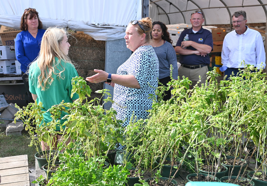 FARM TALK —Shawna Candella Papale and her daughter, Sara, talk with the group of state Assembly members, including Marianne Buttenschon, D-119, Marcy, about their farm and business, Candella's Farm and Greenhouses, 9256 River Road in Marcy, on Tuesday. Buttenschon hosted a tour of six local farms in the Mohawk Valley for several fellow Assembly members, including Aileen Gunther, D. Billy Jones, Jen Lunsford, Jaime Williams, Catalina Cruz, Agricultural Committee Chairperson Donna Lupardo, and Brian Miller, R-101, New Hartford, for visiting some of the great farmers and business leaders in the 119th District,'' Buttenschon said, and to help educate and inform them on issues facing the agricultural industry in her district and across New York. In addition to Candella's, the tour also made stops at R. Jones Nursery and Landscaping Center in Rome; DiNitto Farms, Sciortino Farms and Buttenschon Tree Farm in Marcy; and the Collins Farm Creamery in Rome.