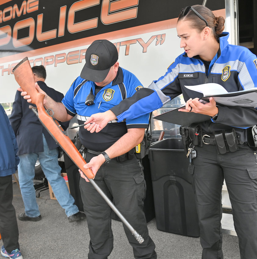 LOGGING IT IN — Rome Police Department patrolmen Anthony Calandra, left, and Jenna Kiskiel check a rifle for serial number at the gun buyback event Wednesday afternoon in the parking lot of St. Paul's Church on Cypress Street. The event, sponsored by the New York State Attorney General's Office, collected 84 firearms, officials said.