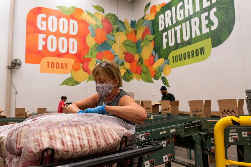 EXTRA HELP — Volunteers pack boxes of food for distribution, at The Capital Area Food Bank Tuesday in Washington.                                         (AP Photo)