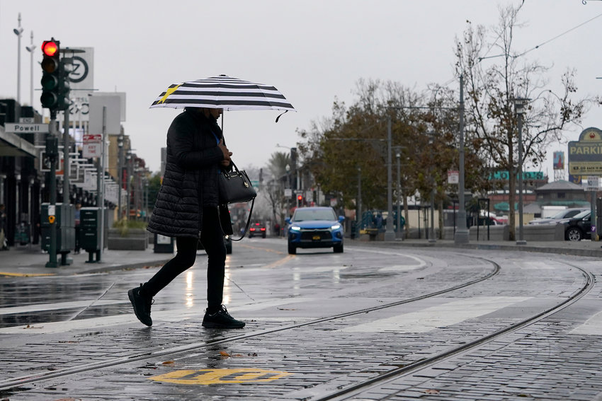 WET SEASON — A pedestrian carries an umbrella while crossing a street at Fisherman's Wharf in San Francisco Wednesday. Showers drifted across the drought-stricken and fire-scarred landscape of Northern California, trailed by a series of progressively stronger storms that are expected to bring significant rain and snow into next week, forecasters said.