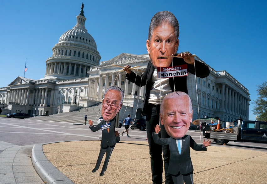SIDEWALK STATEMENT — A climate change demonstrator mocks Sen. Joe Manchin, D-W.Va., who has blocked President Joe Biden's domestic agenda at the Capitol in Washington this week.