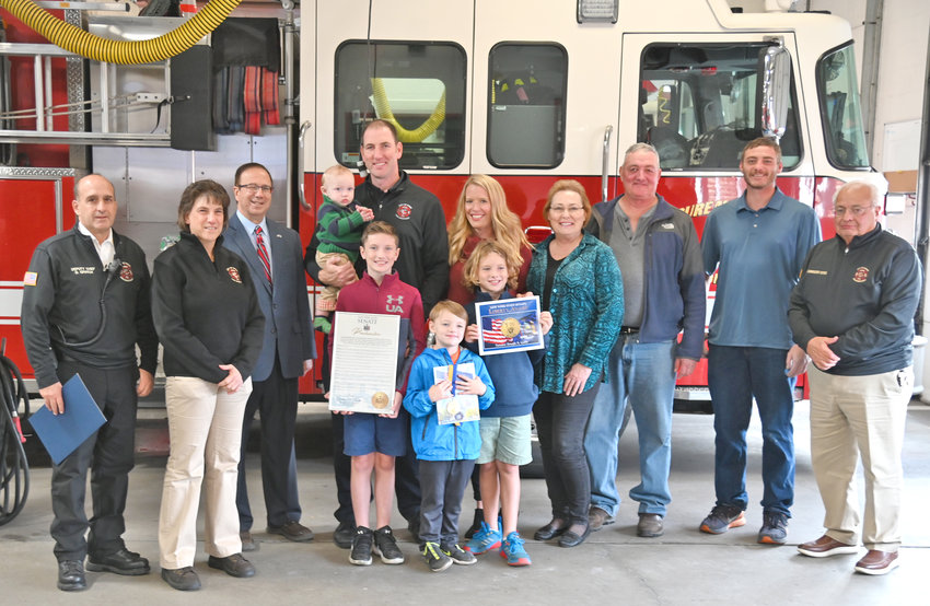 PROUD TOWNSEND family — Rome Fire Lt. Brian Townsend, center, accepted the Liberty Medal from Senator Joseph Griffo Friday afternoon at the Central Fire Station for his heroic, off-duty efforts responding to a boat crash in Herkimer County in September 2020. From left, Deputy Fire Chief David Gratch, Mayor Jacqueline Izzo, Griffo, Brian Townsend holding his 9-month-old son Crew, along with children Charlie, 10, Spencer, 5, and Parker, 7, Ashley Townsend, his wife, Joanne and BJ Townsend, his mother and father, brother Scott Townsend, and Public Safety Commissioner Frank Retrosi.