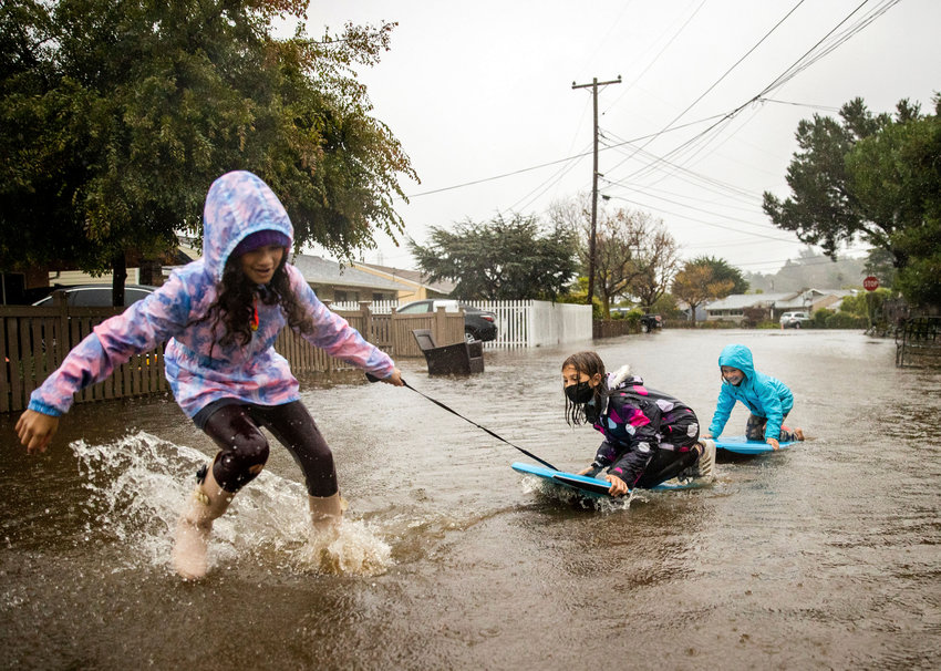 TIME TO PLAY — Children play in floodwaters on Robin Road in Mill Valley, Calif. Strong storms hit part of southern California over the weekend.