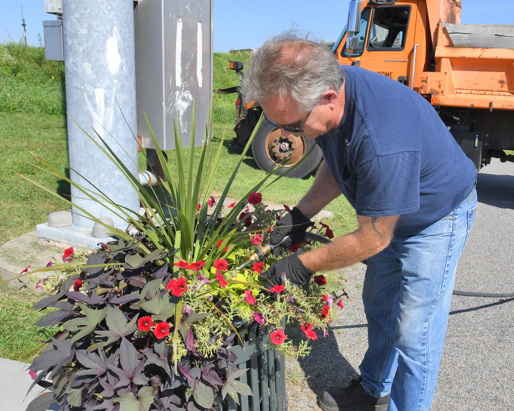 KEEPING IT QUENCHED — Bill Cadrette, an employee with the City of Rome Department of Public Works, waters one of the city's 80 self-watering flower pots. Cadrette said the pots, which are designed to retain water, need steady refreshing in the hot summer sunshine because as soon as the pots are filled up the plants suck up the water to remain hydrated. In addition to the flower pots, workers and volunteers have dozens of flower beds throughout the city to also keep watered.  (Sentinel photo by John Clifford)