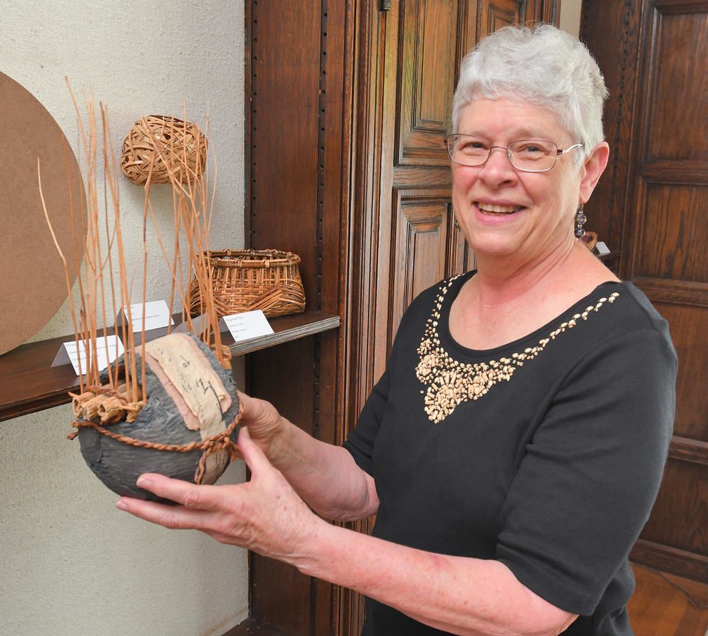 "CAREFUL WORK — Flo Hoppe holds one of her pieces, Interior/Anterior, on display at Rome Art and Community Center. She noted that the time it takes to weave a basket varies greatly depending on the size and complexity. ""I can make some small ones in an hour and then there are the ones like in the exhibit that take a week or more.""  (Sentinel photo by John Clifford)"