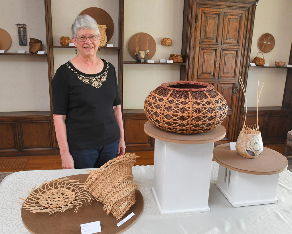 "FAVORITE PIECE — Weaver Flo Hoppe poses with with her baskets, from left, Hashimoto, Intermezzo, and Les Fleursat the Rome Art and Community Center. ""Intermezzo"" is Hoppe's favorite piece. ""It did take a week or more to make and I loved adding all the embellishments that make it so special.""  (Sentinel photo by John Clifford)"