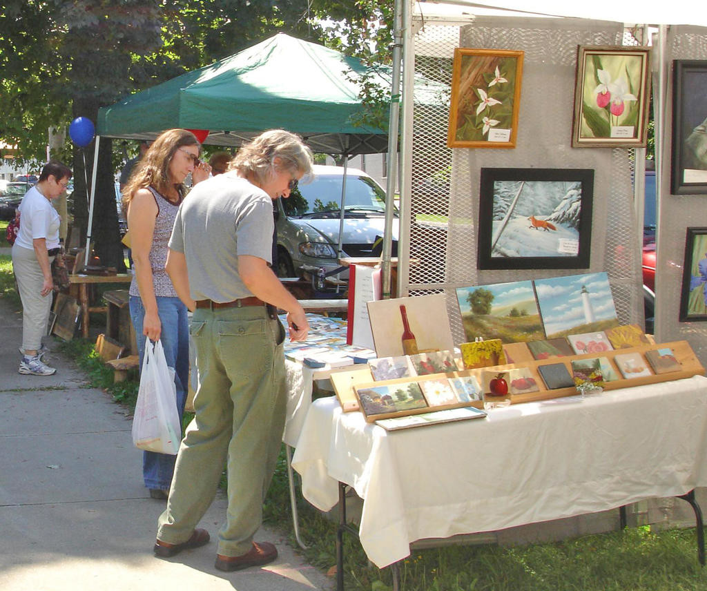 ART GALORE — Arts enthusiasts check out all the masterpieces on display for purchase in the Village Green at the annual Clinton Chamber of Commerce Arts & Music Festival.
