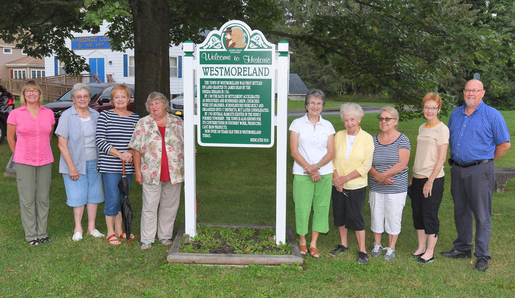 HISTORIC SIGN — Members of the James Dean Chapter of Questers unveiled the new historic town sign on Aug. 14 they held fund-raisers for to replace in the Town Green. From left: Kate Krumdieck, Linda Crumb, Norma Warner, Riley McFadden, Sandy Rolewicz, Bev Miller, Theresa McFadden, Sharon Yager and Town Supervisor Ken Eisnor.  (Clinton Record photos by John Clifford)