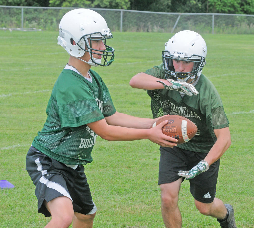 HANDING OFF — Westmoreland quarterback Dakota Collins hands off to running back Mike Alloggio during a recent practice at Westmoreland Elementary School.  (Clinton Record photo by Kenny Kudrewicz)