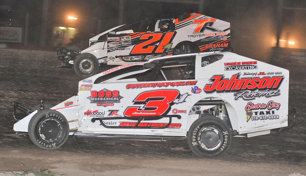 BATTLE FOR SECOND — Marc Johnson, in the No. 3J car, and Peter Britten in the No.21A car, duke it out for second place in the modified feature after Matt Sheppard checked out on the field during Sunday night's race at Utica-Rome Speedway.  (Sentinel photo by John Clifford)