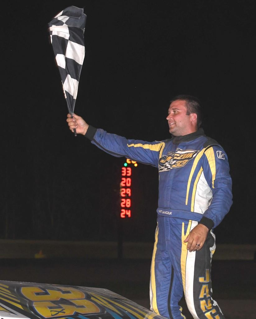 WAVING THE CHECKERED —  Matt Janczuk celebrates his sportsman win at Utica-Rome Speedway on Sunday night.  (Sentinel photo by John Clifford)
