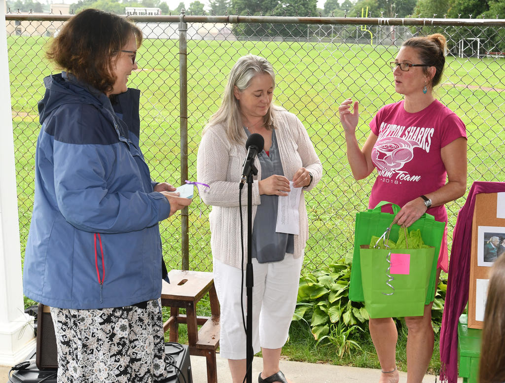 PAVILION DEDICATION — Stacy Butcher, right, Jack Boynton Community Pool board member, talks about the gifts presented to Kate Chiquoine Stamm, left, during the dedication of the new pool pavilion named in honor of her mother, Ibby Chiquoine on Aug. 11.  Looking on is Clinton Youth Foundation President Alma Lowry.  (Clinton Record photo by John Clifford)