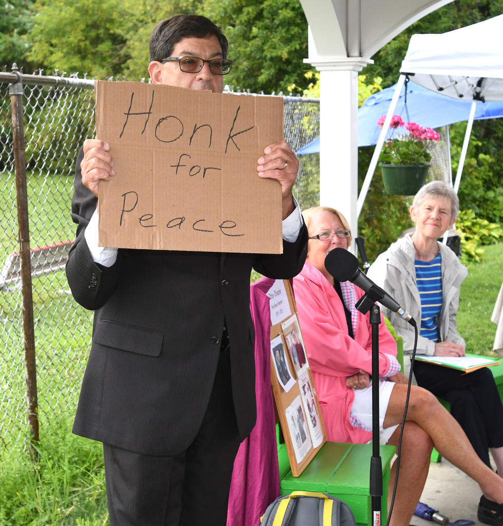 "A 'PEACE' OF IBBY — Former Clinton Elementary Principal Steven Marcus holds up a ""Honk for Peace"" sign that he said Ibby Chiqoine always had with her throughout the village as he shared remarks during Saturday's pool pavilion dedication.  (Clinton Record photo by John Clifford)"