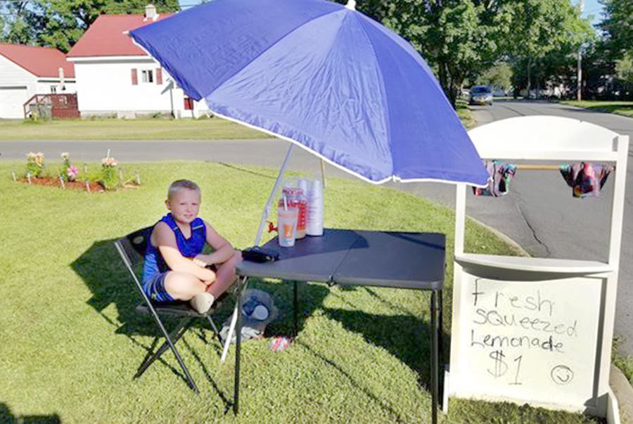 YOUNG ENTREPRENEUR — Eight-year-old Xander Zyla, of Rome, sits in the shade as he man's his lemonade stand on the corner of Hamilton and Liberty streets last week.  Zyla said he opened the stand to raise money to go to Canada.  (Photo submitted)