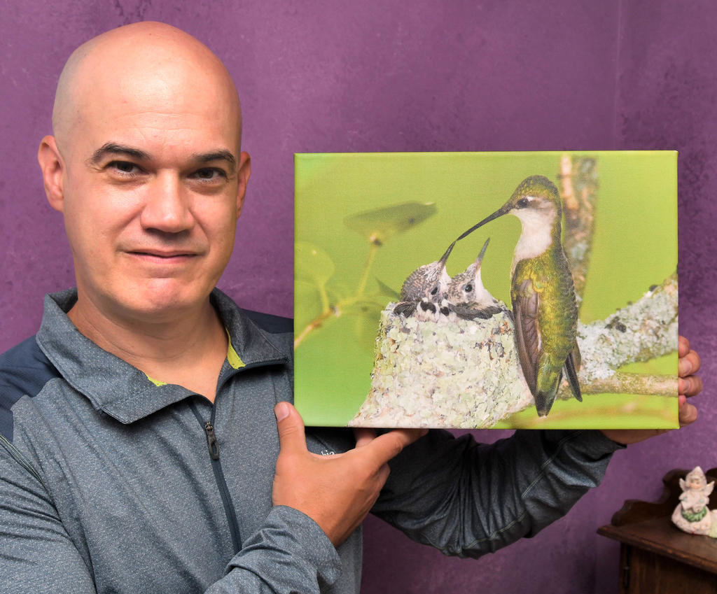 PRIZED PHOTO — Jody Hildreth, of Waterville, with his photo of a female ruby throated hummingbird feeding her young he named Mother's Touch.  (Clinton Record photo by John Clifford)
