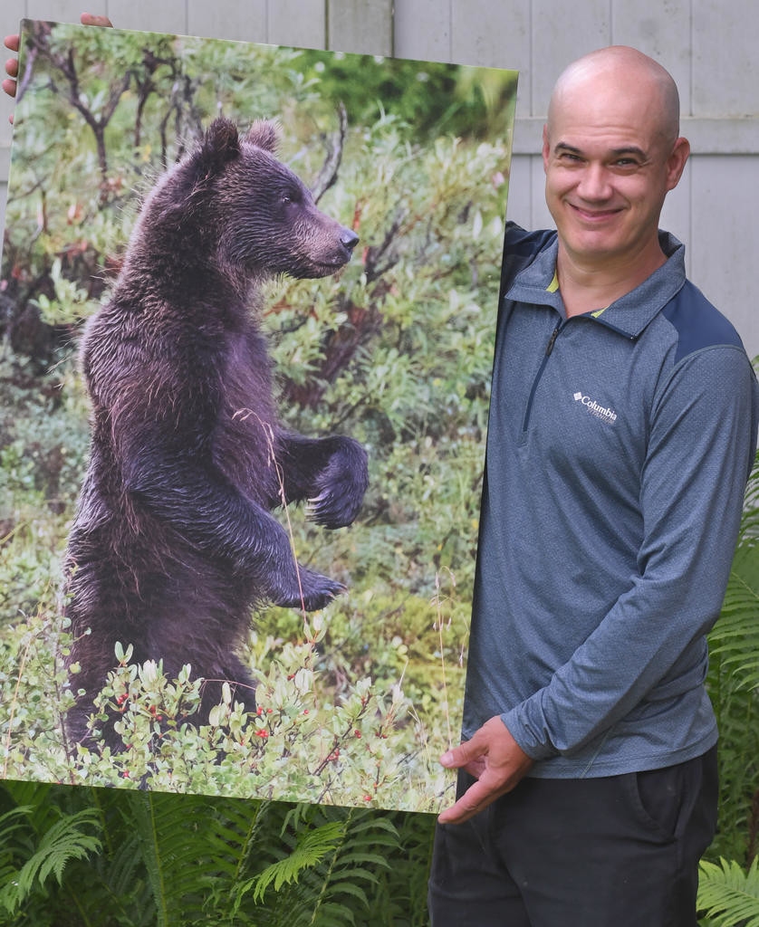 STAND TALL — Jody Hildreth, of Waterville, holds a canvas enlargment of a grizzly bear he photographed in the Denali National Park in Alaska.  (Clinton Record photo by John Clifford)