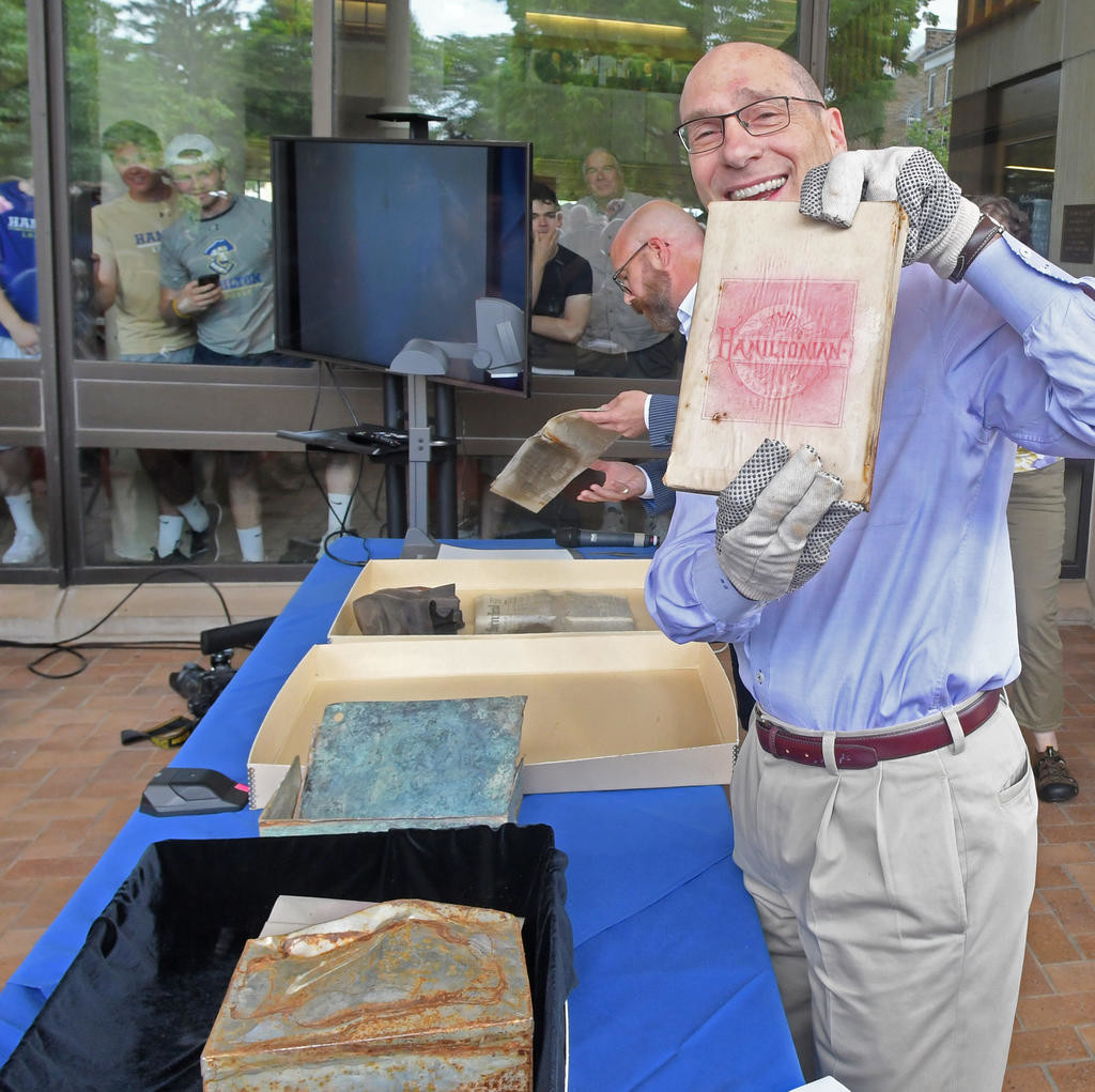 PHOTO FRIENDLY — Hamilton College President David Wippman is all smiles as he displays the Hamiltonian yearbook that was inside the school's 1890 time capsule.  In the background is Mark Tillson, Hamilton's special collections coordinator. Officials on Tuesday opened the time capsule, which was unearthed during a street construction project.  (Sentinel photo by John Clifford)