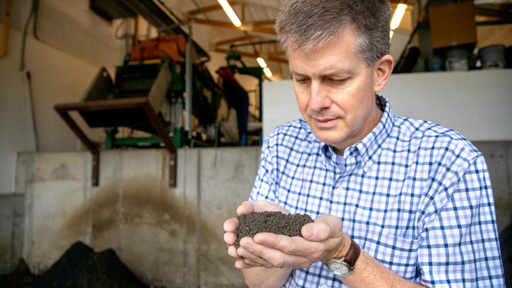 RESULT — Paul Jennette, director of biocontainment operations at the College of Veterinary Medicine, examines separated sand.  (Jason Koski / Cornell Marketing Group)