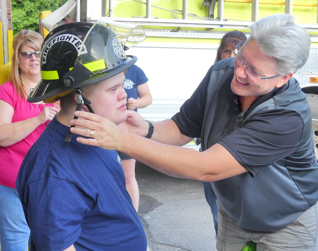 HIS OWN HELMET — Thirteen-year-old Joey Abt is gifted a Lee Center fire helmet by Firefighter Carol Kieffer during his visit to the Stokes-Lee Center Road fire station Tuesday night. Joey's mother, Diane, looks on.
