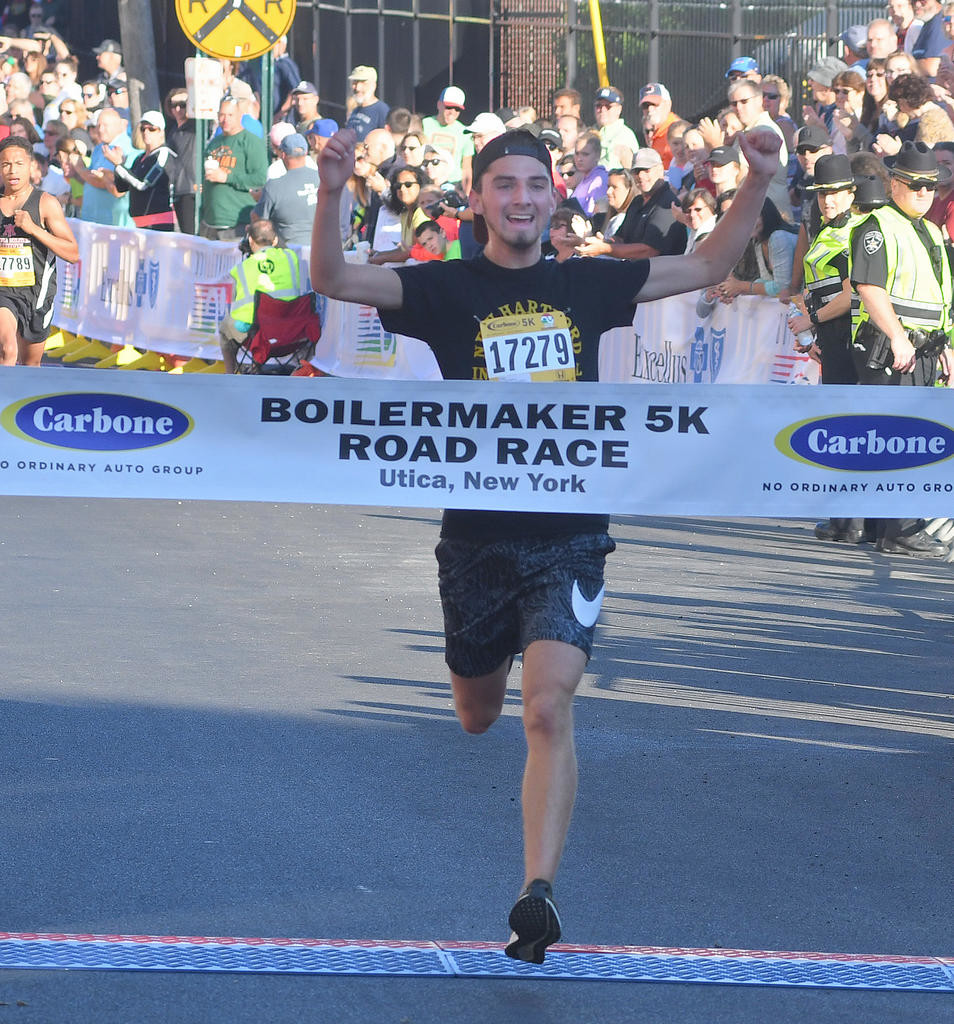 FINAL STRIDES — Boonville's Tyler Fauvelle crosses the finish line as the winner of the Boilermaker 5k Men's Race on Sunday in Utica. Fauvelle crossed the finish line in 16 minutes and 12 seconds for the win.  (Sentinel photo by John Clifford)