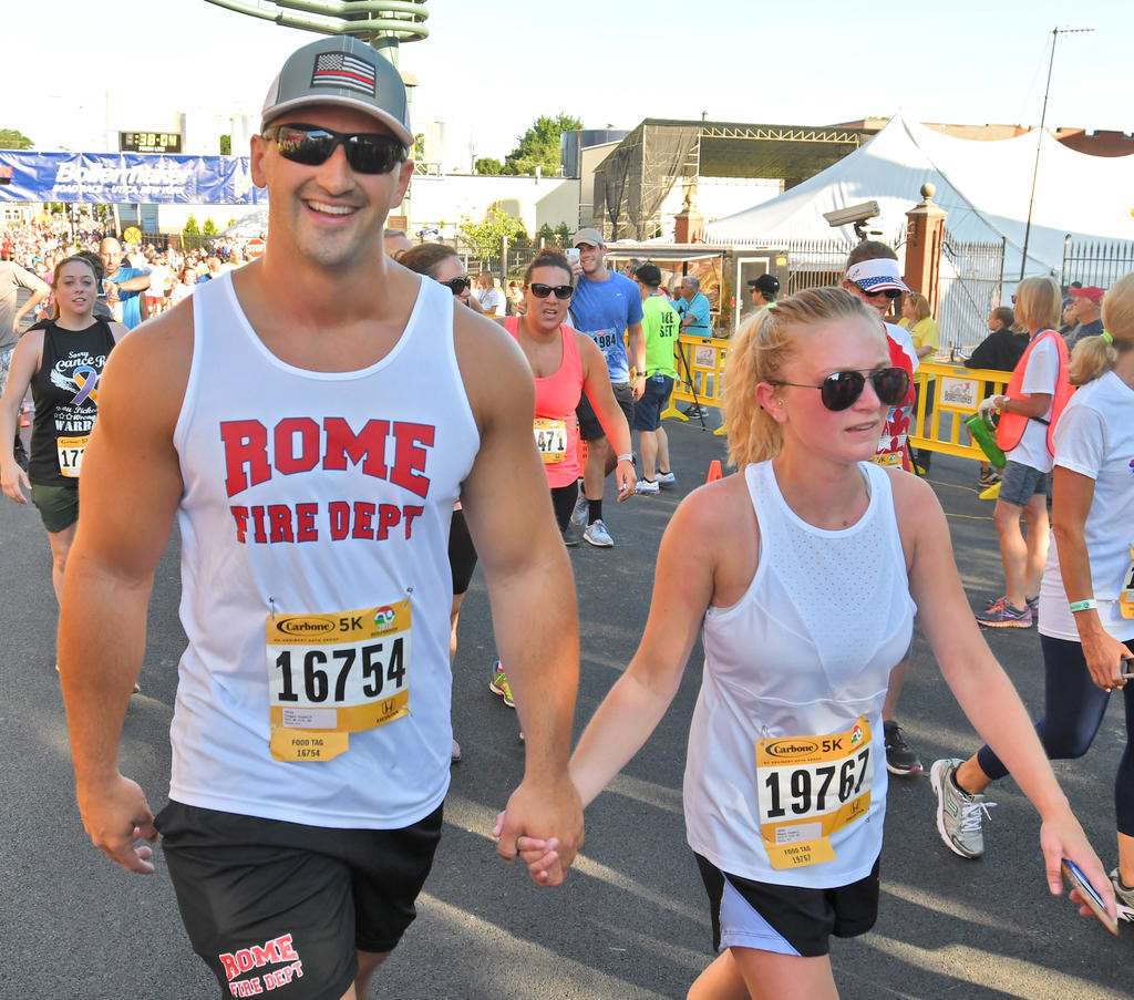 FINISHING TOGETHER — Rome Fireman Dustin Colgan, left, and Caitlin Shean also from Rome at the conclusion of the Boilermaker 5k race on Sunday in Utica.  (Sentinel photo by John Clifford)