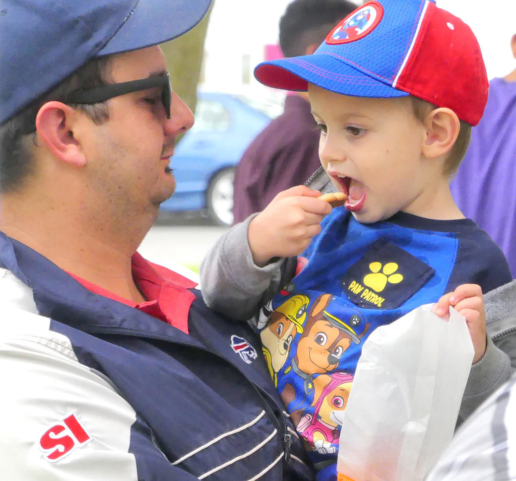 FATHER-AND-SON TIME — Brant Lasher and his 2-year-old son Anderson Lasher enjoy quality time and cookies at the  Clinton Farmers Market June 7.  (Clinton Record photo by John Clifford)