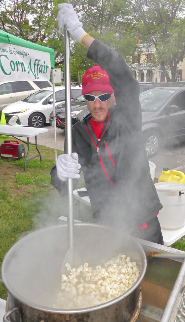 CHURNING AND TURNING — Adam Bell of Gramma and Grandpa's Kettle Corn Affair, keeps the popcorn popping in the kettle at the Clinton Farmers Market on June 7. The vendor has been coming to the farmers market since 2000.  (Clinton Record photo by John Clifford)