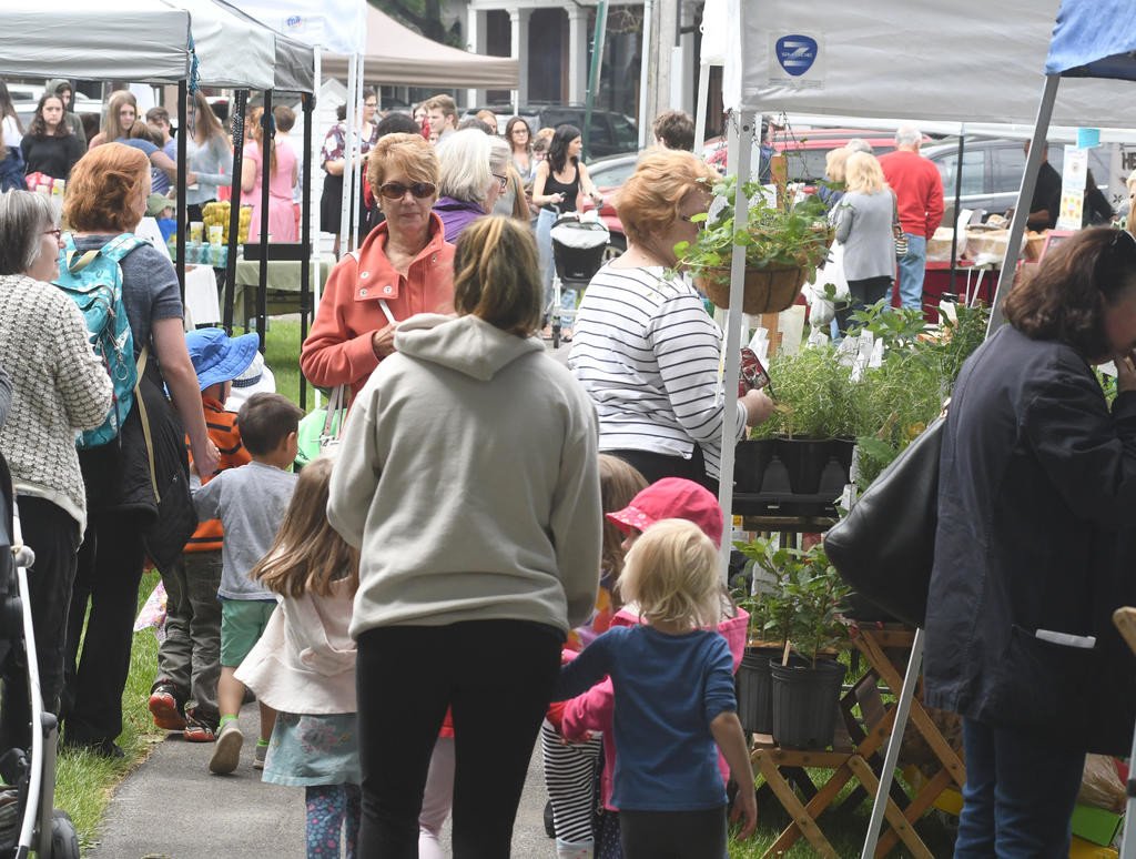 BUSTLING BUYERS — Plenty of patrons create busy sidewalks in the Village Green at the Clinton Farmers Market on opening day Thursday.  (Clinton Record photo by John Clifford)