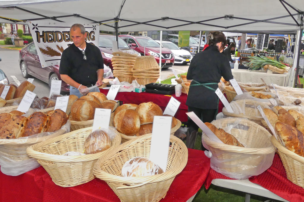BOUNTIFUL BREADS — Teresa and David Bunces of Heidlberg Bread in Herkimer stock their bread baskets at Clinton Farmers Market Thursday.  (Clinton Record photo by John Clifford)
