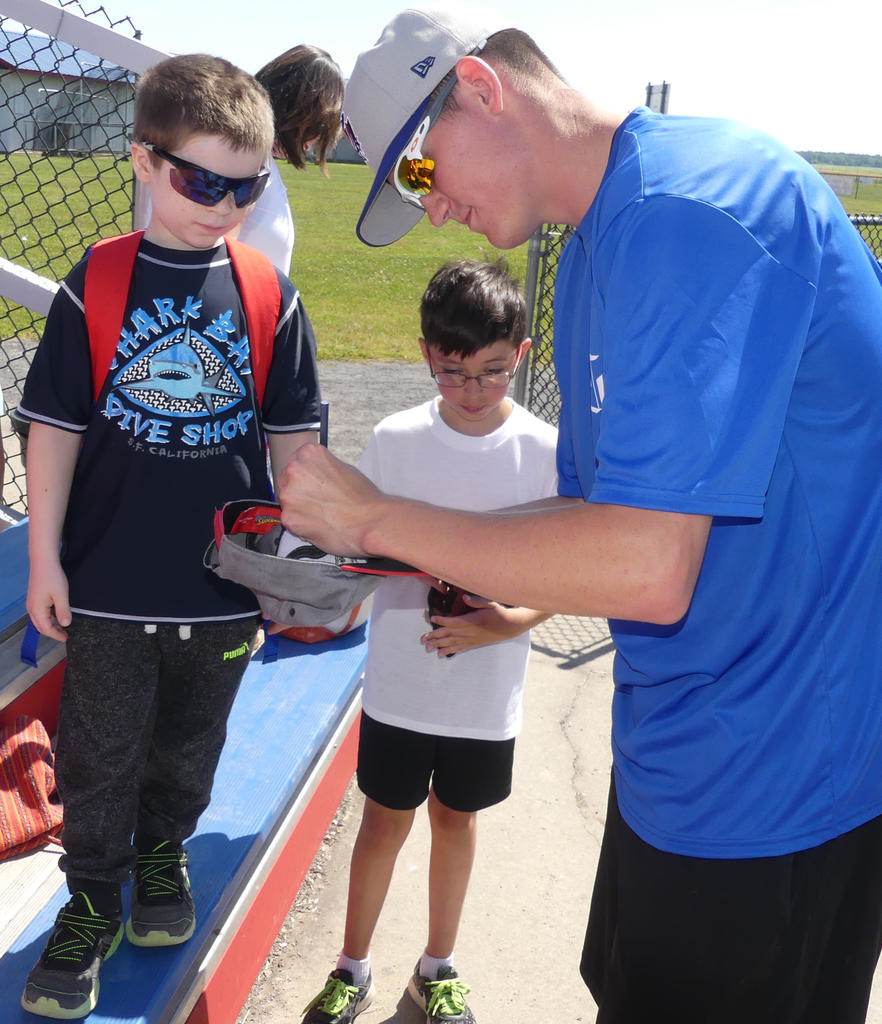 HAT SIGNING — Rome Generals pitcher Kevin Simon signs an autograph for Ridge Mills 3rd grader Mathew Mooney prior to the start of the Generals game against Sherrill Silversmiths.  (Sentinel photo by John Clifford)