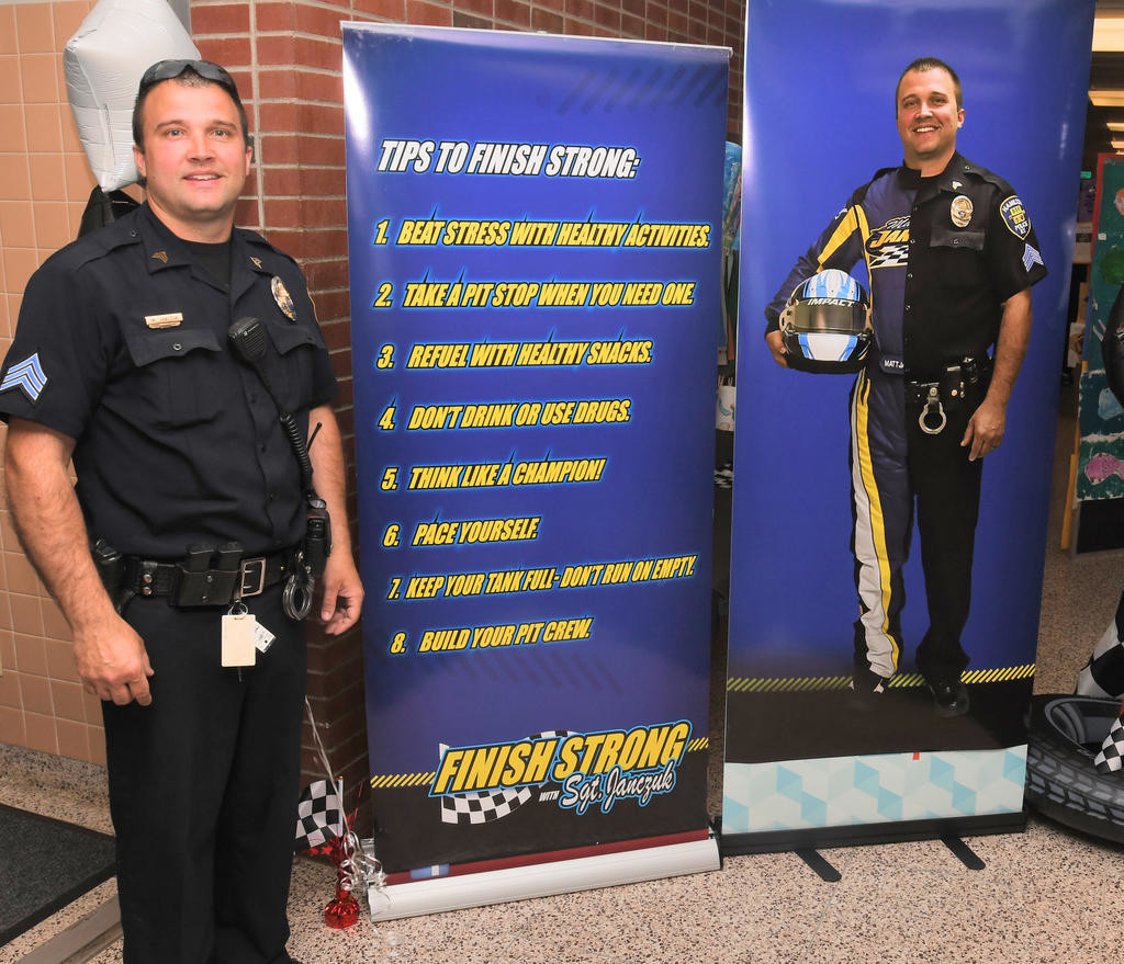 TIPS — Sgt. Matt Janczuk with the poster that will greet students each day until the end of the year. In addition, there are posters and reminders of tips placed all over the school.  (Sentinel photo by John Clifford)