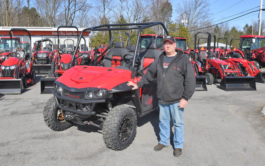 BUSINESS ON THE MOVE — Todd Bortiatynski, who operates Hobby Hill Farm Sales at 8727 Turin Road in Lee, stands with some of the Mahindra-brand vehicles that his business offers. He plans to relocate to the nearby former Berkshire Bank branch building at 6310 Elmer Hill Road, which is being purchased by Bortiatynski's business.  (Sentinel photo by John Clifford)