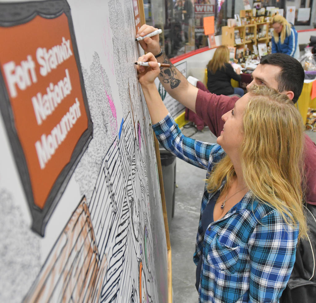 COLOR TIME — Destiny Wishart and James Breen add their creative touches to a giant coloring project at the Rome Home Expo on Saturday. Visitors, with markers in hand, helped color a giant mural of Fort Stanwix National Monument.