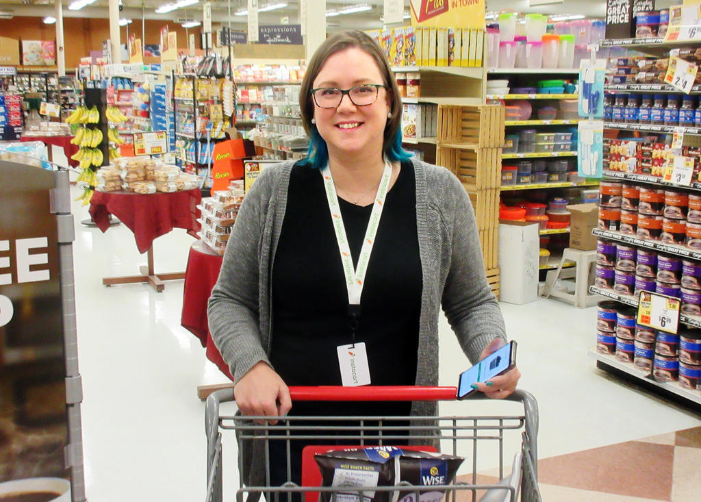 HERE TO HELP — Pampered Chef consultant Jamie Makin shops for the Tops Instacart program at the Rome Tops store. Shoppers who use the program can pre-order their grocery lists, have them picked up and then delivered.  (Sentinel photo)