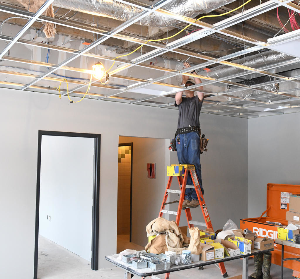 BRIGHTENING THINGS UP — Mark Odle of the Oneida Electrical company installs light fixtures in office space at Strough Middle School's 801 Laurel St. building, as part of a renovation project. District officials are hopeful that the project will be done on time for occupancy of the building in September 2018.  (Sentinel photos by John Clifford)