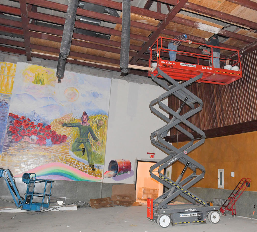 "NOT IN KANSAS ANYMORE — With art depictions from ""The Wizard of Oz"" in the background, work proceeds on beams in the auditorium at Strough Middle School's 801 Laurel St. building.  (Sentinel photo by John Clifford)"