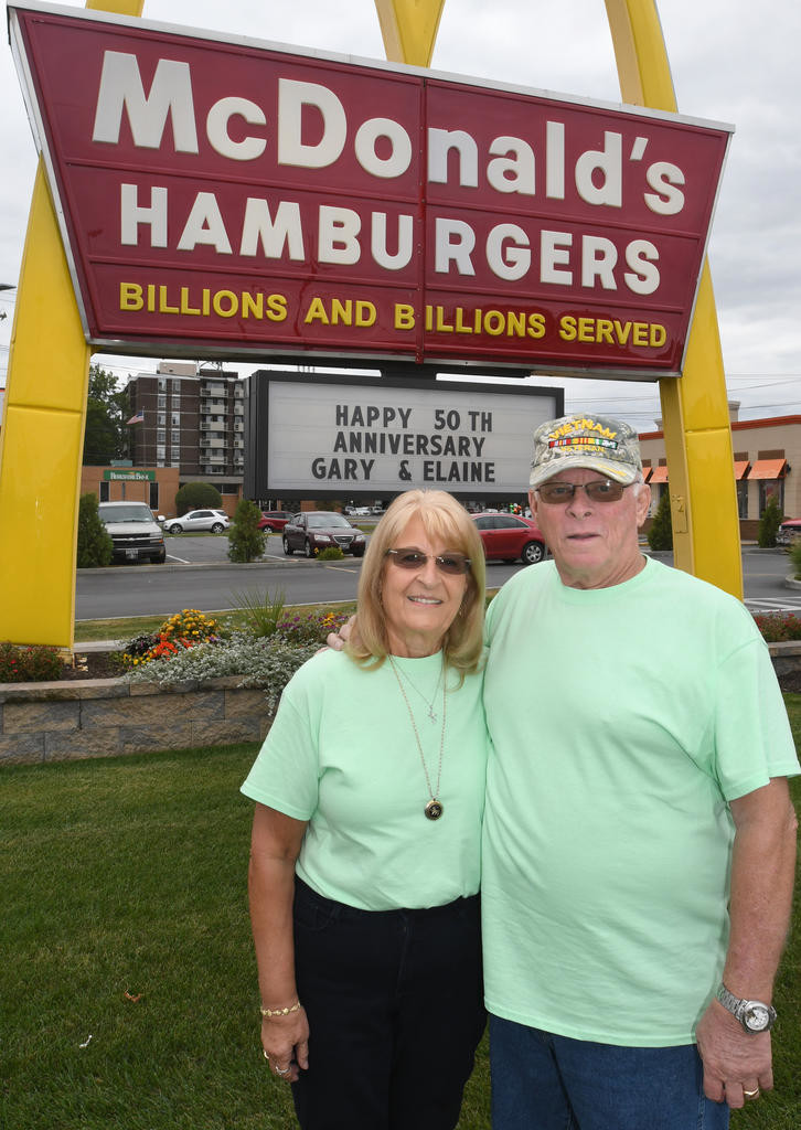 GOLDEN ANNIVERSARY — Gary and Elaine Neidl, of Ocoee, Fla., formerly of Rome, stand in front of the sign at the McDonald's restaurant on Black River Boulevard, where they met 52 years ago.  The couple recently celebrated their 50th wedding anniversary. (Sentinel photo by John Clifford)