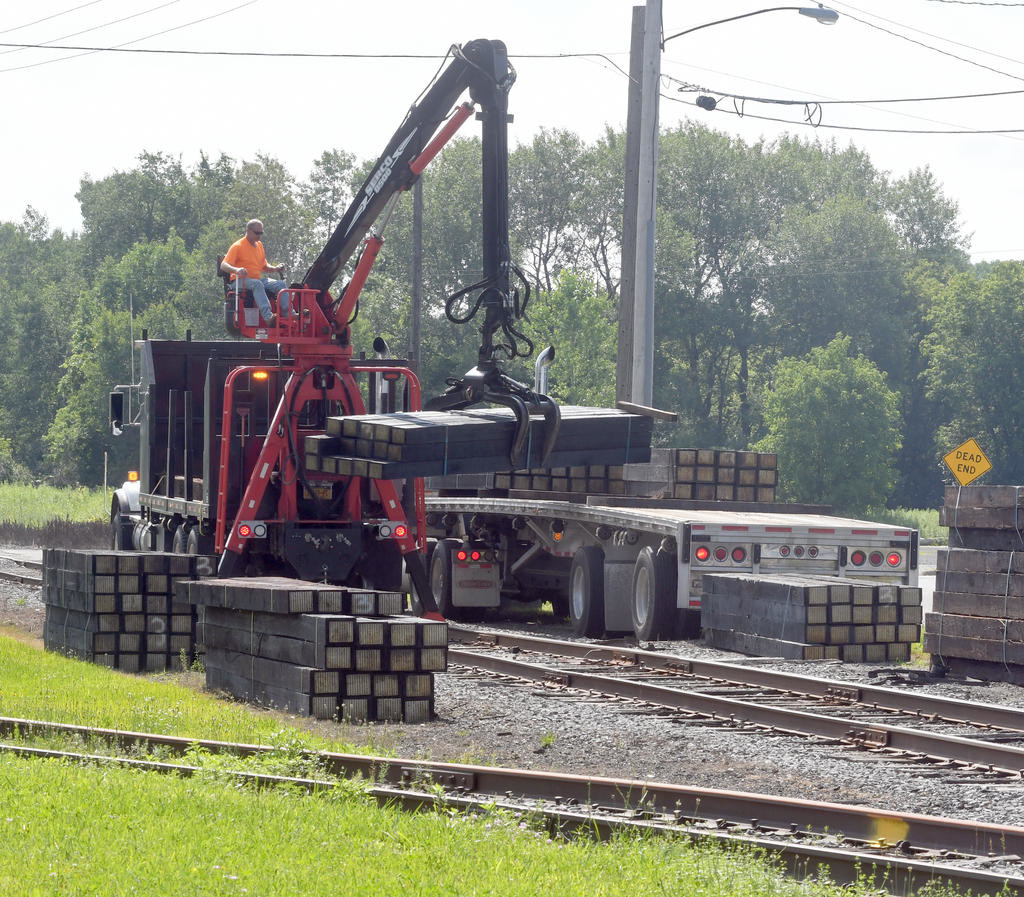 Railroad ties are off loaded from a flatbed on      Rome Daily Sentinel