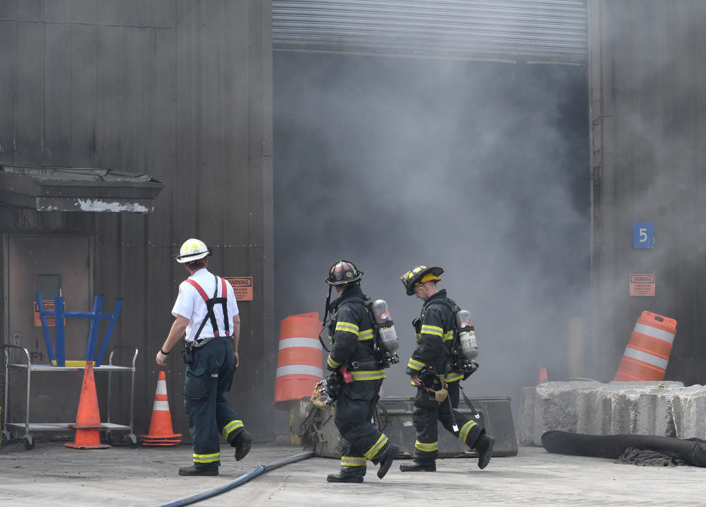 SMOKE ON THE GARBAGE — Deputy Fire Chief Mark S. Kohlbrenner, left, leads his firefighters around the smoke at the transfer station on Perimeter Road Thursday afternoon.  (Sentinel photo by John Clifford)