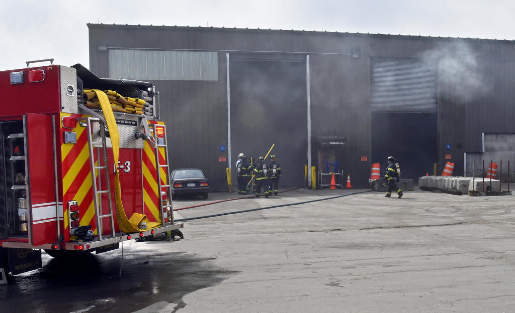 HOLD YOUR NOSE — Firefighters head inside the Solid Waste Authority transfer station to put out a flaming pile of garbage Thursday afternoon.  (Sentinel photo by John Clifford)