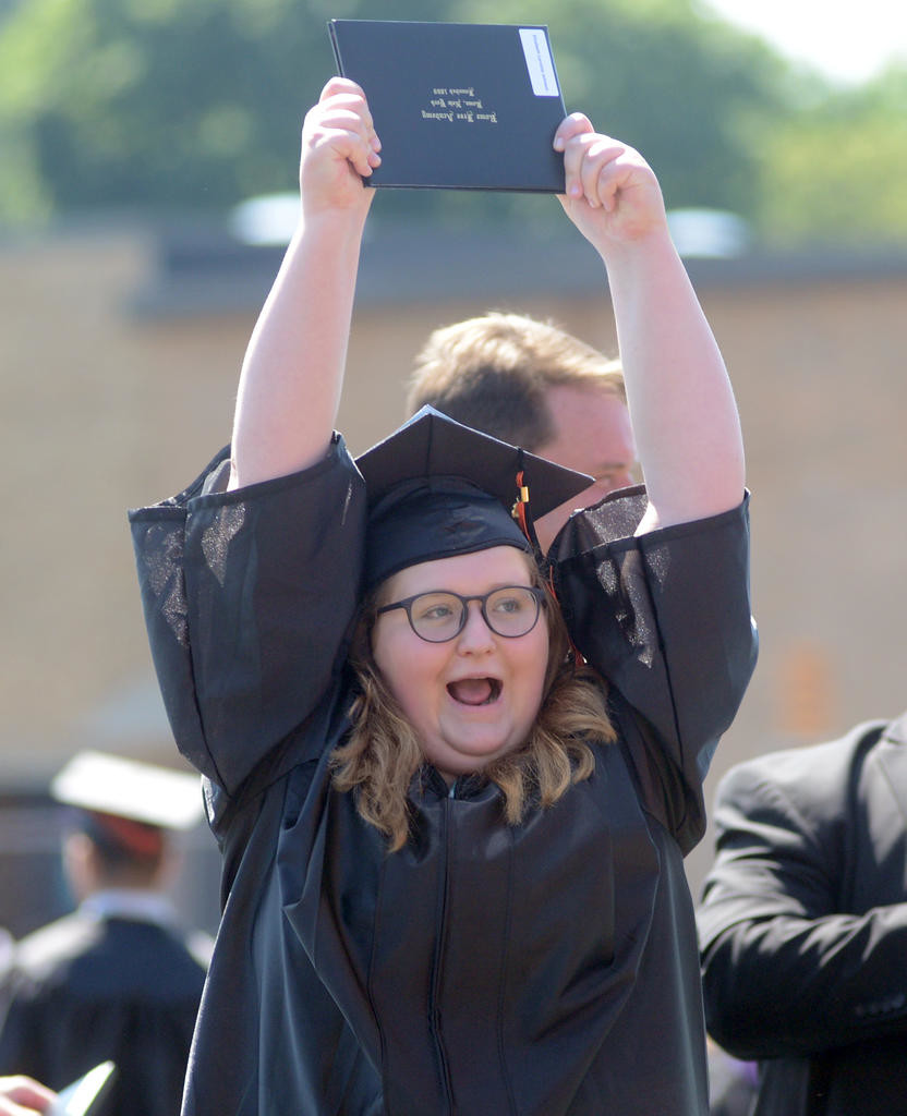 A happy Elizabeth Johnson holds up her diploma  (Sentinel photo by John Clifford)