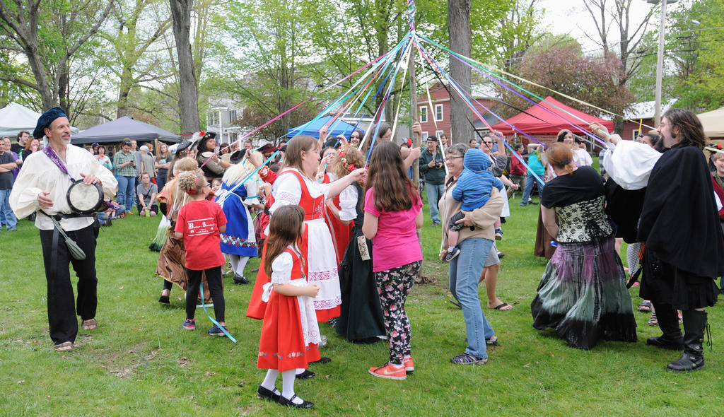 CELEBRATING SPRING — Festival participants wrap multi-colored ribbons around a maypole as music plays at the sixth annual Mayfaire on the Green on Saturday in Holland Patent. Other entertainment at the two-day event included plays, puppeteers, fire twirling, dance performances, live music, and armored combat. More photos, page 3 and online at www.romesentinel.com.  (Sentinel photo by Makenzi Enos)