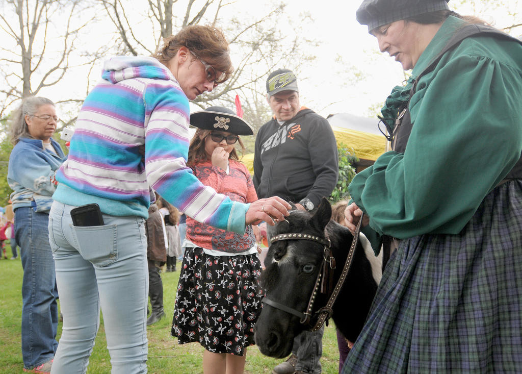 People stop to pet and take photos of the miniture pony as they walk the Mayfaire in Holland Patent.  (Sentinel photo by Makenzi Enos)