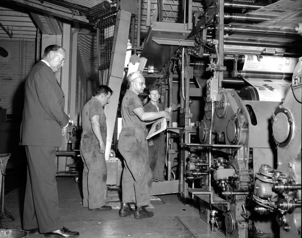 INVESTING — Publisher Bradley C. Barnard, left, watches press foreman Carl Domino, in the press hat, roll the letterpress newly installed in 1956. The family invested in radio, new technology, and new buildings including the downtown offset printing plant at 333 W. Dominick St. built in 1971 during urban renewal.