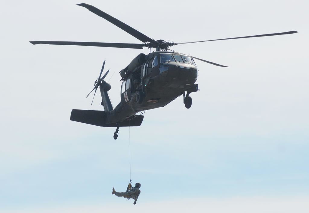 A member of the National Guard propelling from the helicopter to perform a lift.  (Sentinel photo by Makenzi Enos)